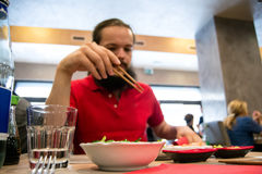 Delighted man / customer in red shirt eating Chinese / Japanese food in a restaurant.  Stock Photo