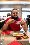 Delighted man / customer in red shirt eating Chinese / Japanese food in a restaurant.  Royalty Free Stock Photos