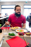 Delighted man / customer in red shirt eating Chinese / Japanese food in a restaurant.  Stock Image