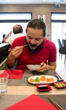 Delighted man / customer in red shirt eating Chinese / Japanese food in a restaurant. With a mouth wide open Royalty Free Stock Photo
