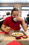 Delighted man / customer in red shirt eating Chinese / Japanese food in a restaurant. With a mouth wide open and a funny face Stock Photo