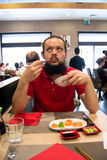 Delighted man / customer in red shirt eating and looking upwords in a Chinese / Japanese restaurant Stock Image