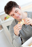 Delighted man eating bread in the kitchen Stock Photography
