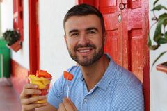 Delighted man eating a fruit platter royalty free stock photo