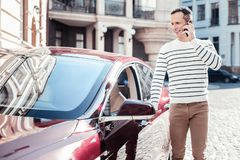 Delighted man opening his car. Favorite place. Smiling male person holding telephone near his ear and turning head while standing near his auto stock image