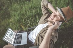 Delighted man is resting on field while having phone conversation. Work outdoors. Top view of cheerful relaxed guy is sitting in chair on meadow and talking on royalty free stock photos