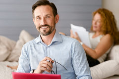 Delighted man sitting and smiling at home Stock Images