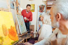 Delighted man teaching people in painting studio. Stock Images