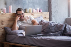 Delighted man using his laptop while lying in a bed Stock Photo