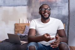 Delighted man watching TV in bedroom. Enjoy film. Delighted African young man watching TV and sitting in bedroom while relaxing Royalty Free Stock Photos