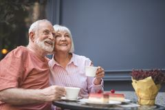 Delighted man and woman bonding to each other in cafe. Waist up portrait of smiling couple sitting at table and drinking tea outside. They are hugging and Stock Images