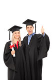 Delighted man and woman in graduation gowns Royalty Free Stock Image