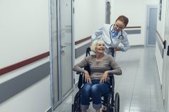 Merry doctor is pushing wheelchair with patient. Delighted mature lady is feeling nice while sitting in pushchair. Attentive practitioner is helping her move in stock photo