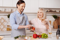 Delighted mature son helping aged mother cooking in the kitchen Stock Photos
