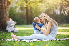 Delighted mother with her son outdoors in a park Stock Photos