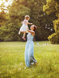 Delighted mother tossing her lovely child Royalty Free Stock Images