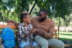 Delighted nice boy taking a new watch. Small present. Delighted nice boy looking at his father while taking a watch royalty free stock images