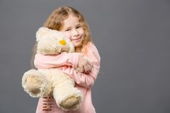 Delighted nice girl hugging her toy royalty free stock photo