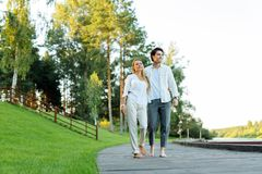 Delighted nice happy couple walking together barefooted. In the nature. Delighted nice couple walking together barefooted while enjoying the nature stock photos