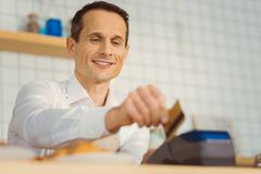 Delighted nice man holding a credit card royalty free stock photo