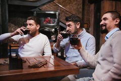 Delighted nice men having beer. Resting together. Delighted nice pleasant men holding glasses with beer and watching football while resting together in the pub stock image