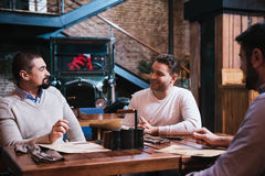 Delighted nice men having a discussion. Pleasant conversation. Delighted nice good looking men sitting together and discussing something while meeting in the pub royalty free stock photo