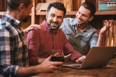 Delighted nice men looking at their friend. We are happy for you. Delighted nice positive men looking at their friend and smiling while sitting at the laptop stock photography