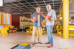 Delighted nice men visiting a bowling club. Favourite pastime. Delighted nice men visiting a bowling club while resting together at the weekends royalty free stock photo
