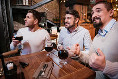 Delighted nice men watching football game. Game for men. Delighted nice handsome men sitting at the table and watching a football game while enjoying their beer stock photo