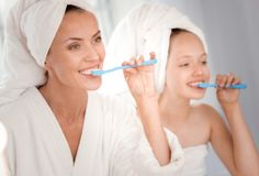 Delighted nice woman brushing teeth together with daughter Stock Image
