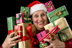 Delighted Old Lady Hugging a Dozen Wrapped Gifts Royalty Free Stock Photos