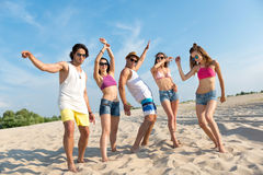Delighted overjoyed friends standing on the beach Royalty Free Stock Image