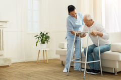 Delighted positive caregiver helping her patient. Do not hurry. Delighted positive cheerful caregiver smiling and helping her patient to stand up while being royalty free stock photo
