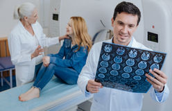 Delighted positive doctor holding CT scan results Stock Photo