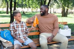 Delighted positive father and son cheering with drinks. Pleasant refreshment. Delighted positive father and son cheering with drinks while sitting together on stock images