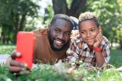 Delighted positive father and son taking selfies. Happy memories. Delighted positive father and son taking photos while lying together on the grass stock images
