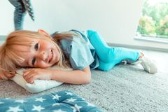 Delighted positive girl lying on the cushion. Feeling comfortable. Delighted positive girl lying on the cushion while feeling comfortable stock image