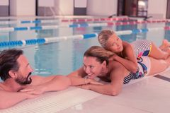 Delighted positive girl lying on her mother. So comfortable. Delighted positive girl lying on her mother while having fun with her in the pool stock image