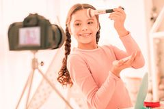 Delighted positive girl using her makeup tools. Professional brush. Delighted positive girl using her makeup tools while applying cosmetics royalty free stock photo