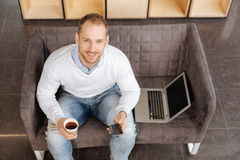 Delighted positive man holding his smartphone Royalty Free Stock Photo