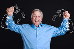 Delighted positive man standing against the black background Royalty Free Stock Image