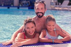 Delighted positive man standing behind his wife and daughter. Father and husband. Delighted positive men smiling while standing in the pool behind his wife and royalty free stock images