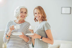 Delighted positive mother and her adult daughter drinking coffee Stock Photo