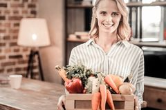 Delighted positive woman holding a box with vegetables. Absolutely fresh. Delighted positive blonde woman holding a box with vegetables and smiling while looking Royalty Free Stock Photo
