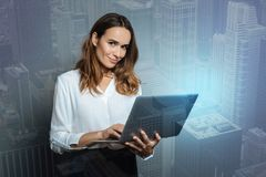 Delighted positive woman holding a laptop. Electronic device. Delighted nice positive woman holding a laptop and working on it while being in a positive mood royalty free stock photography