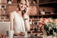Delighted positive woman making a call. Phone call. Delighted positive cheerful woman holing her phone and making a phone call while being ready to take notes Stock Photo