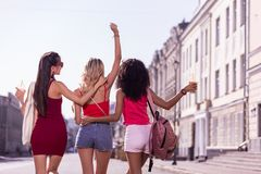 Delighted positive young women walking in the city stock images