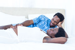 Delighted pregnant woman lying on bed with her husband Stock Images