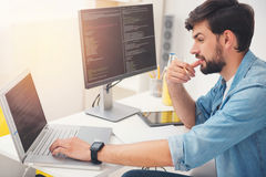 Delighted programmer working on a laptop. Thinking about it. Delighted young concentrated programmer working on a laptop and coding while sitting in an office royalty free stock photography
