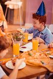 Delighted red haired boy wearing paper hat. Favorite food. Handsome child expressing positivity while having festive dinner stock photography
